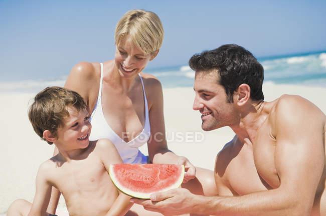 Family enjoying watermelon on sandy beach — Stock Photo