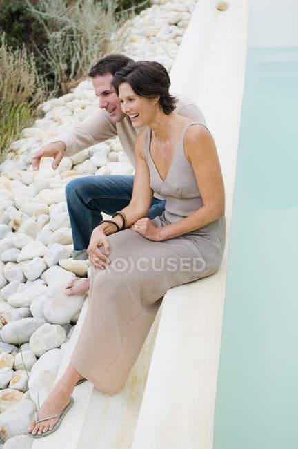 Сміється пари, сидячи біля басейну та милуючись видом — стокове фото