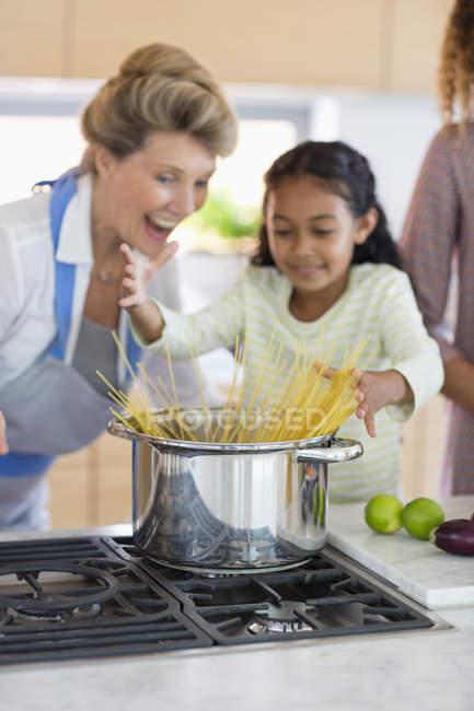 Старша жінка з внучкою готує їжу на кухні — стокове фото