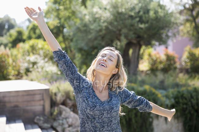 Glückliche Frau mit ausgestreckten Armen stehend im Garten — Stockfoto