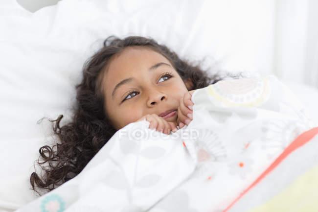 Verträumtes kleines Mädchen liegt auf dem Bett — Stockfoto