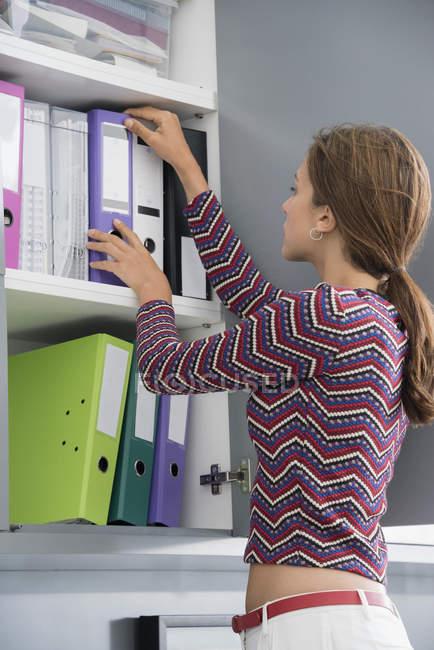 Jovem empresária procurar arquivo no escritório — Fotografia de Stock