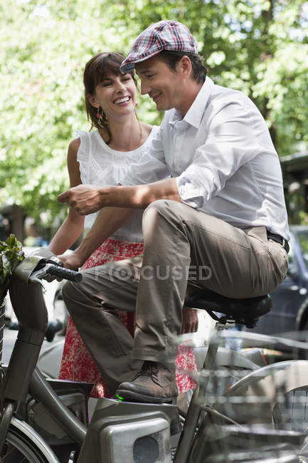 Smiling couple sitting on bicycles and talking in city — Stock Photo