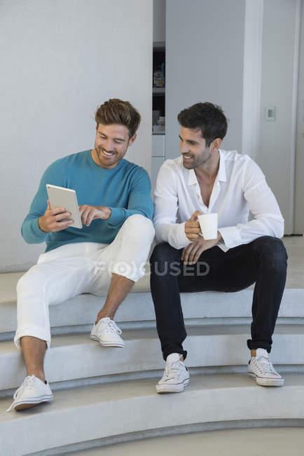 Amigos varones felices usando tableta digital en escaleras - foto de stock