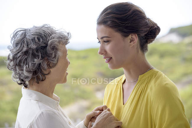 Portrait of loving mother and daughter holding hands outdoors — Stock Photo