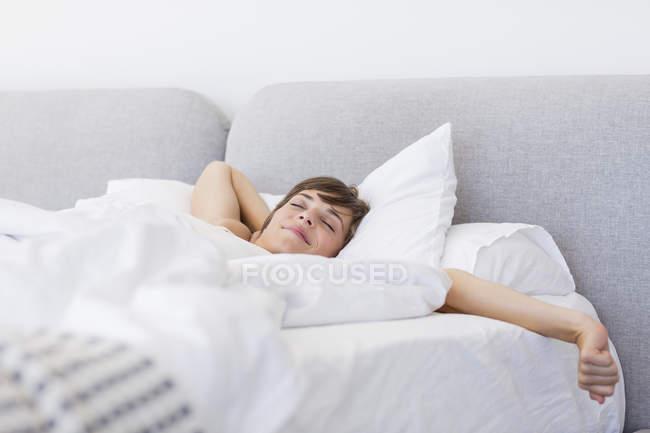Joven despierta y el bostezo con estiramiento en la cama - foto de stock