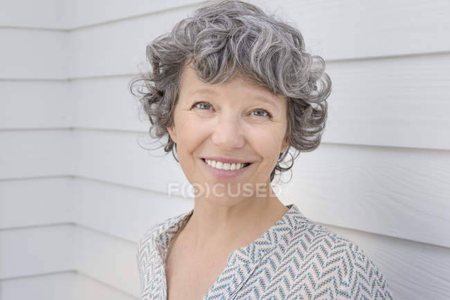 Portrait of happy mature woman in front of white wall — Stock Photo