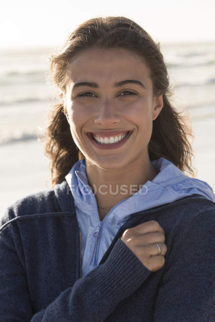 Portrait of charming young woman in warm hoodie smiling on beach — Stock Photo