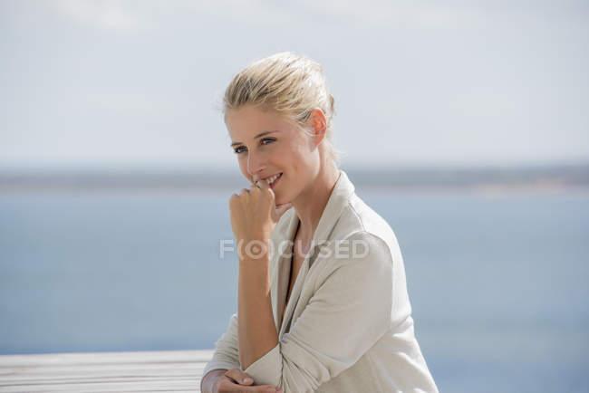 Молодий усміхається жінка, сидячи за столом, на березі озера — стокове фото