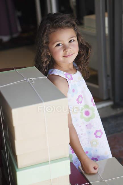 Ritratto di ragazzina carina in piedi davanti a una pila di scatole — Foto stock
