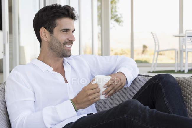 Homem feliz desfrutando xícara de café no terraço — Fotografia de Stock