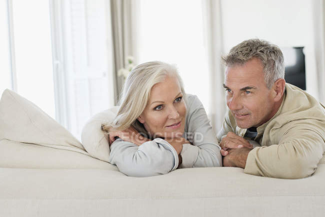 Thoughtful senior couple resting on bed at home — Stock Photo