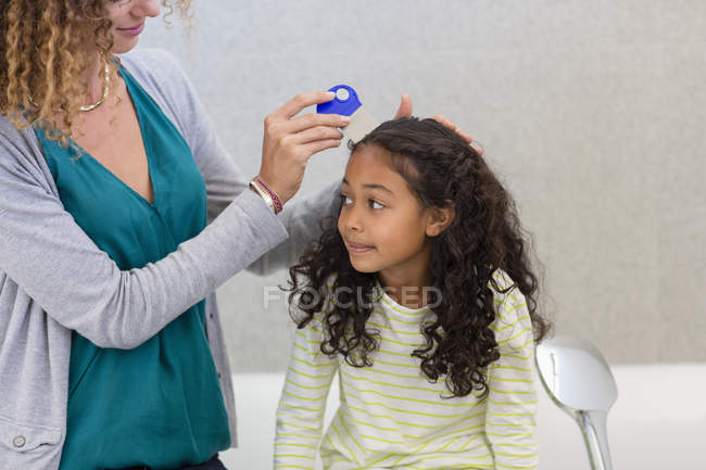 Madre con peine de piojos en el pelo de la hija en el baño - foto de stock