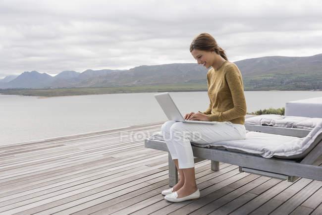 Smiling young woman using laptop on lake shore — Stockfoto