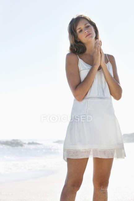 Женщина, стоящая в молитве позиции на пляже — стоковое фото
