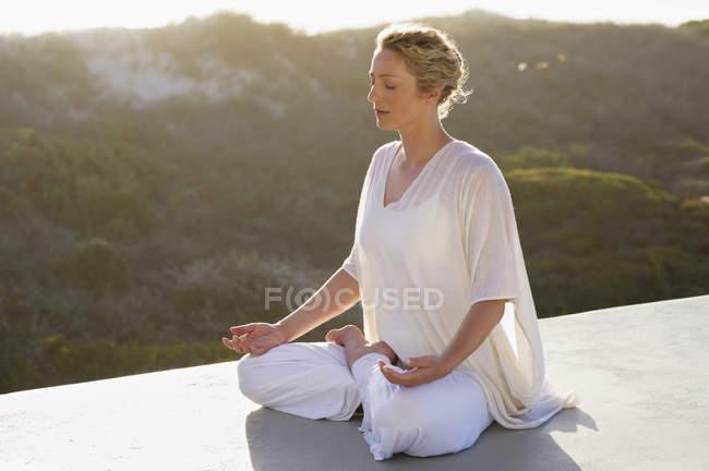 Donna rilassata in abito bianco meditando in natura — Foto stock
