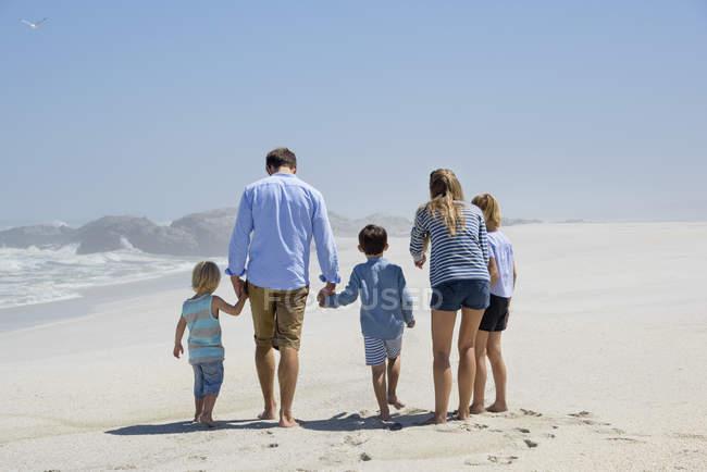 Вид на семью, гуляющую вместе на песчаном пляже — стоковое фото