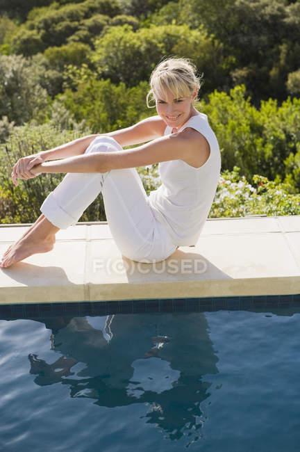 Femme détendue rêveuse assise au bord de la piscine et regardant l'eau — Photo de stock