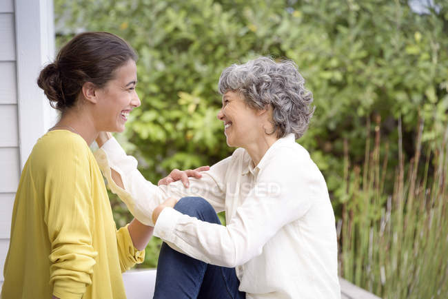 Happy mother talking to adult daughter on porch — Stock Photo