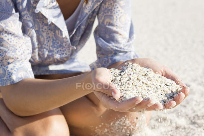 Close-up of female hands holding sand on beach — Stock Photo