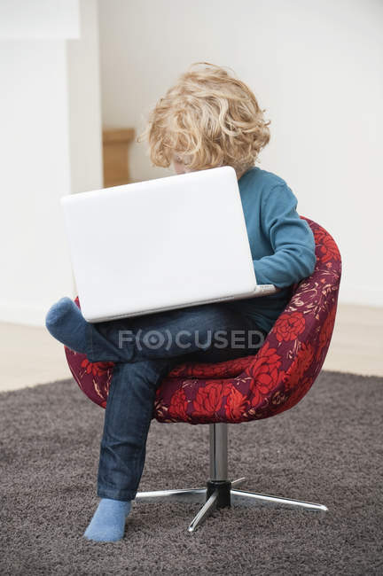 Boy with blonde hair using a laptop in armchair at home — Stock Photo