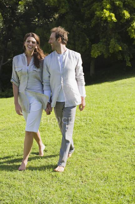 Улыбающаяся пара, гуляющая по траве в солнечном саду — стоковое фото