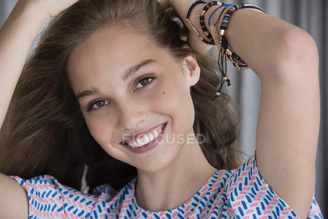 Портрет улыбающейся девочки-подростка с руками в волосах — стоковое фото
