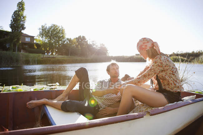 Young couple romancing in boat on lake in nature — Stock Photo