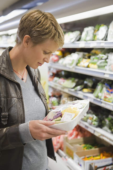Woman buying packed food in supermarket — Stock Photo