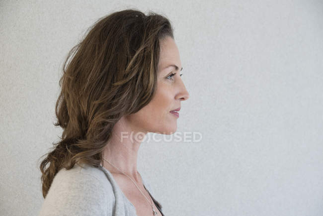 Close-up of happy mature woman looking away on grey background — Stock Photo