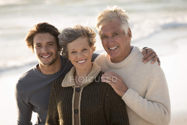 Portrait of happy family standing on beach together — Stock Photo
