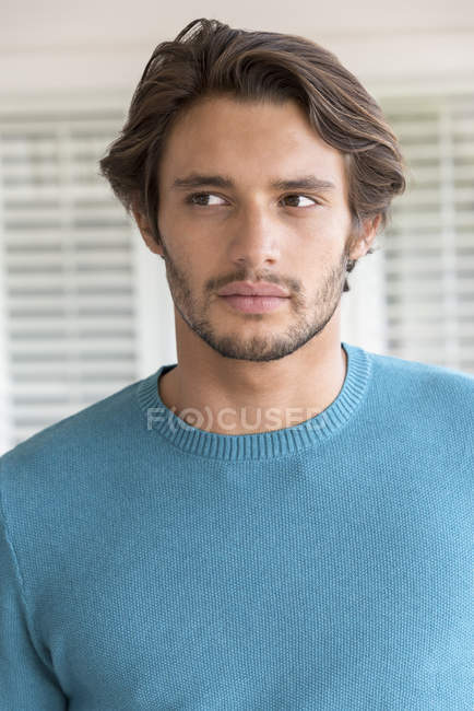 Portrait of thoughtful young man in blue pullover looking away — Stock Photo