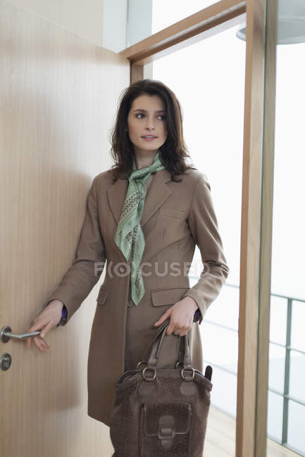 Elegant woman with handbag entering a house — Stock Photo