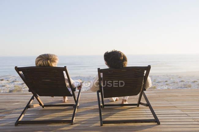 Couple assis sur des chaises longues sur la plage et parlant — Photo de stock