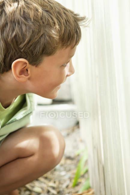 Крупным планом веселого маленького мальчика, прячущегося за оградой — стоковое фото