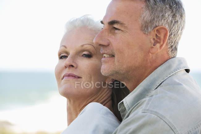 Nahaufnahme eines romantischen Senioren-Paares, das sich am Strand umarmt — Stockfoto