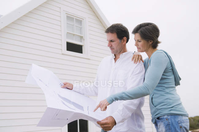 Focused mature couple looking at blueprint of house — Stock Photo