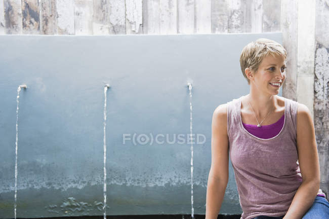Woman with short hair sitting in front of running water from faucets — Stock Photo