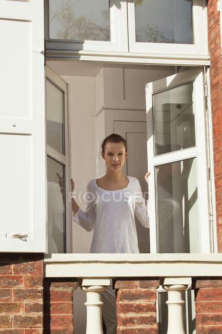Janela de abertura de mulher jovem no apartamento — Fotografia de Stock