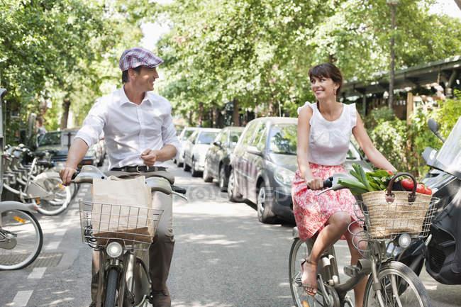Casal carregando legumes em bicicletas na cidade, Paris, Ile-de-France, França — Fotografia de Stock