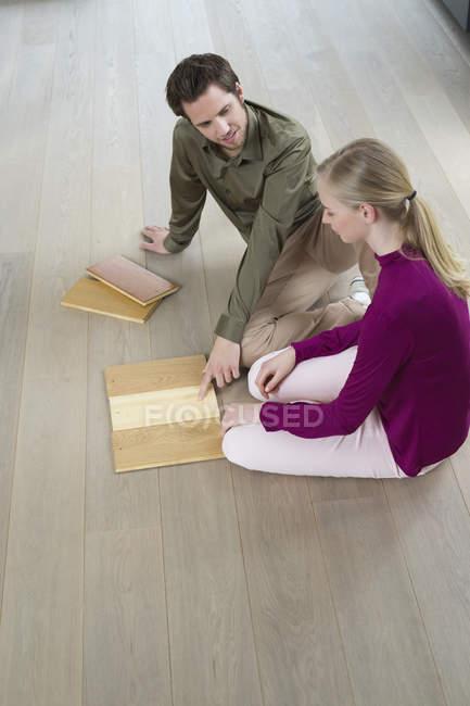 Молодая пара выбирает ламинированные доски, сидя на полу — стоковое фото