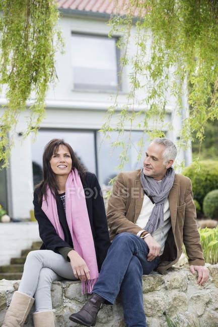 Усміхаючись романтична пара, сидячи в саду в сільській місцевості — стокове фото