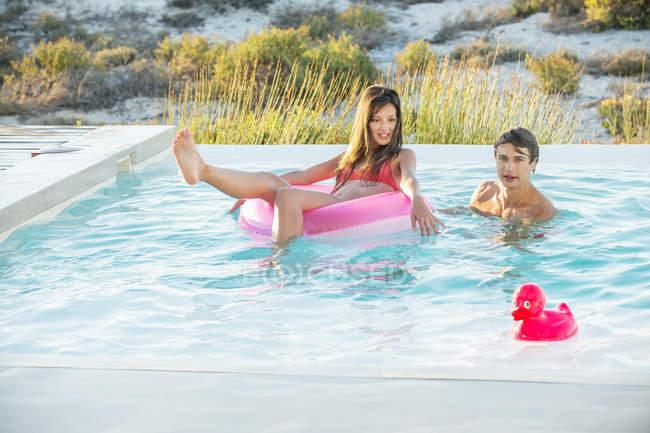 Couple having fun in swimming pool on beach — Stock Photo