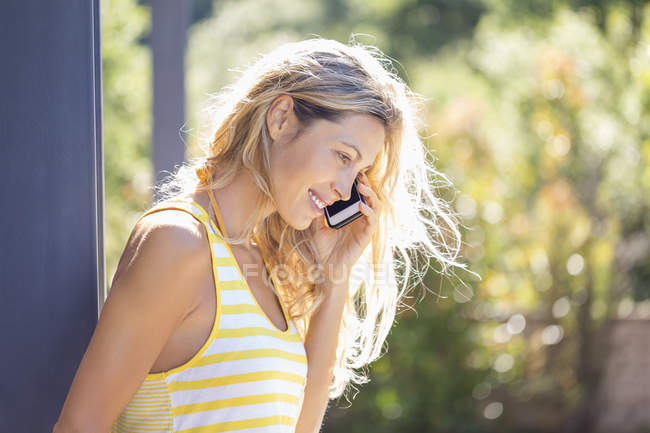 Smiling woman talking on phone in sunny garden — Stock Photo
