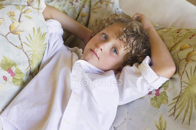 Portrait de petit garçon aux cheveux bouclés couché sur le canapé — Photo de stock
