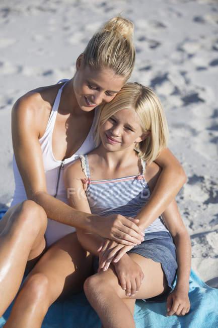 Счастливые женщина и дочь сидят и обнимаются на пляже — стоковое фото