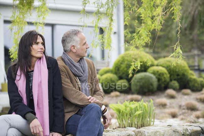 Pareja sentada en jardín en campo y mirando lejos - foto de stock