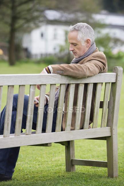Элегантный зрелый человек, с помощью мобильного телефона на деревянной скамейке в парке — стоковое фото