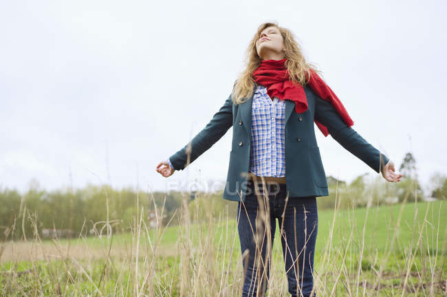 Young woman with eyes closed daydreaming in field — Stock Photo