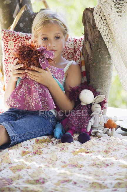 Споглядальний маленька дівчинка тримає іграшки в дерево будинок — стокове фото